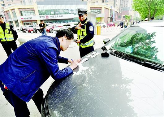 楚天都市报讯 图为一名开车打手机的司机被交警拦停处罚