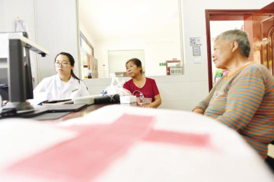 大学生村医杨海燕在村卫生室为村民看病