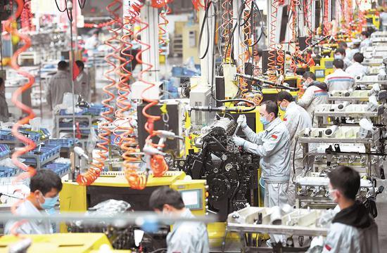 """1月21日,十堰张湾东风商用车公司动力总成事业部,工人在生产拥有自主知识产权的新款商用车动力总成""""龙擎""""。"""
