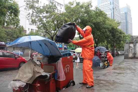 环卫工人将垃圾装车运走