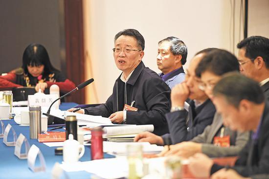 在分组讨论中,白江源委员(左二)就尽快制定我省民族团结进步条例提出建议。(湖北日报全媒记者 李溪 摄)