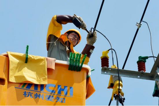 """国网荆门供电公司本着""""能带不停""""的原则,供电职工头顶烈日,在10千伏火山二回开展带电作业,千方百计保障客户用电需求。李翊嘉 汪适文摄"""