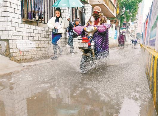 图为电动车把水溅到行人身上