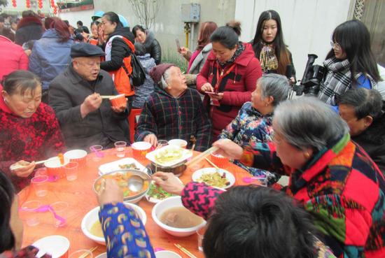 87岁的孤老张桂荣婆婆开心地吃百家宴 王东升摄影