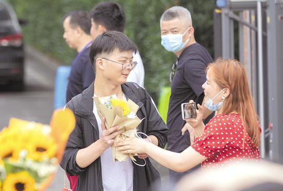 6月9日,华中科技大学附属中学考点,家长为结束高考的考生送上鲜花。 (湖北日报全媒记者 柯皓 摄)