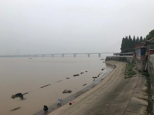 江边上有不少休闲的市民及游客,也有人在江边钓鱼