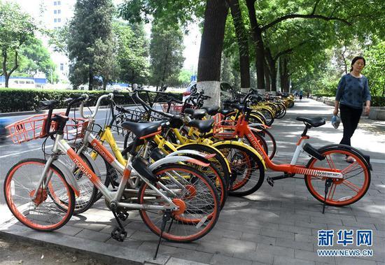 5月25日,一名行人从停放在北京西城区宣武门西大街南侧的共享单车旁走过。新华社记者 罗晓光 摄