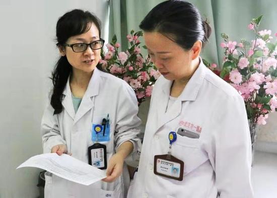 李培凤医生和同事传看表扬信 通讯员代雨朦摄