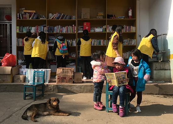 3月22日,志愿者帮忙整理书籍,几个彝族孩子在看书。澎湃新闻记者 张维 图