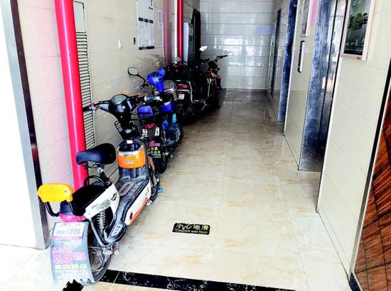 图为:武汉市徐东大街一栋居民楼一楼走廊内停着不少电动自行车。