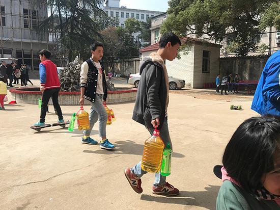 3月23日,爱心人士给子墨艺高送来食品等物资,彝族孩子帮忙搬运。澎湃新闻记者 张维 图