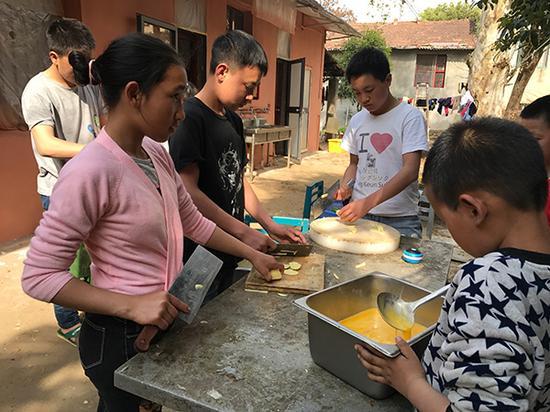 3月28日,安么木扎(左一)和孩子们一起帮厨。澎湃新闻记者 张维 图