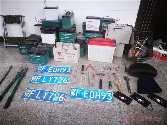 民警收缴的电瓶40余块、假车牌4个、作案工具一箱