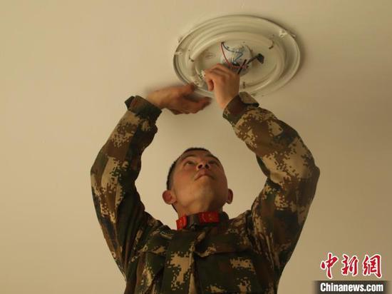 韩晓晖在修理电灯 李子扬 摄