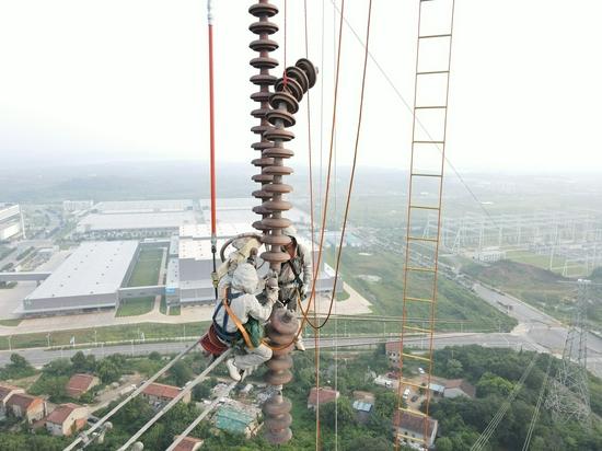 国网湖北检修公司职工冒着35℃高温,在70米高空中完成了夏凤二回上相四片自爆绝缘子带电更换,消除了影响线路运行的危急缺陷,保障了湖北主网安全稳定运行。