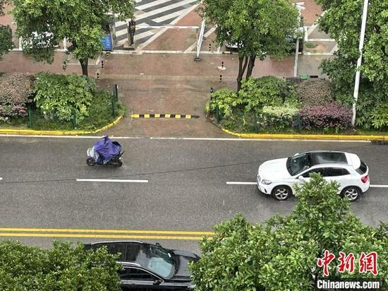 17日中午,武汉市民冒雨出行 马芙蓉 摄