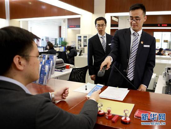 这是工作人员为天津花生好车汽贸有限公司董事长陈鹏云(左一)扫码登记。新华社发