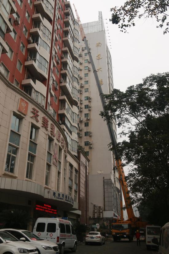 通讯员 王凯 谢靓   200多吨的大型吊车把120多米高的吊臂伸到21层楼顶,施工人员在双层保险带的保护下高空作业,拆除楼顶的广告牌。20日,江汉区城管委开始拆除位于江汉区新华路南达大楼顶上的超期广告牌。   上午9时许,记者在新华路拆除现场看到,一辆大型吊车正在一栋高层建筑前固定支架,吊车的6节吊臂全部伸出,为能到达21层楼楼顶高度,施工人员还在吊臂顶部加装了一节10多米长的负杆,以增加吊臂长度。楼顶十几个工人正在用氧气切割机,对楼顶广告牌进行切割,地面上的大型吊车,则利用长达120米的吊臂将切