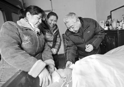二儿子梁占东(右)、四女儿梁晓萍(左)和五女儿梁晓青(中)在照顾老母亲。记者 李葳 摄