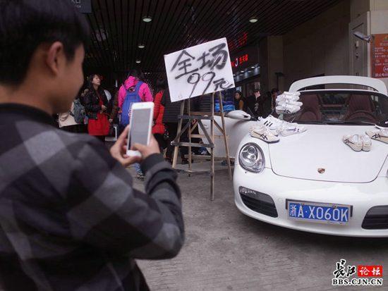 江汉路一男子在豪华跑车上摆摊卖鞋 引众人围观