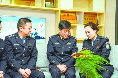 陈默(右一)向同事们展示手机里的微信群 通讯员唐时杰 摄