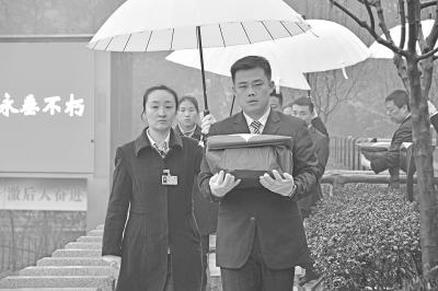 图为陵园工作人员手捧覆盖着国旗的烈士骨灰盒,缓缓走向烈士墓地   摄影李文斌