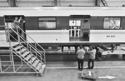 列车被高高架起,维修人员全方位对所有部件进行检修、维护    记者李永刚 摄