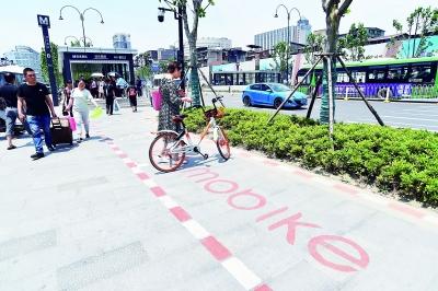 昨天,在汉正街站B口,市民将共享单车停在停车线内。     记者詹松 摄