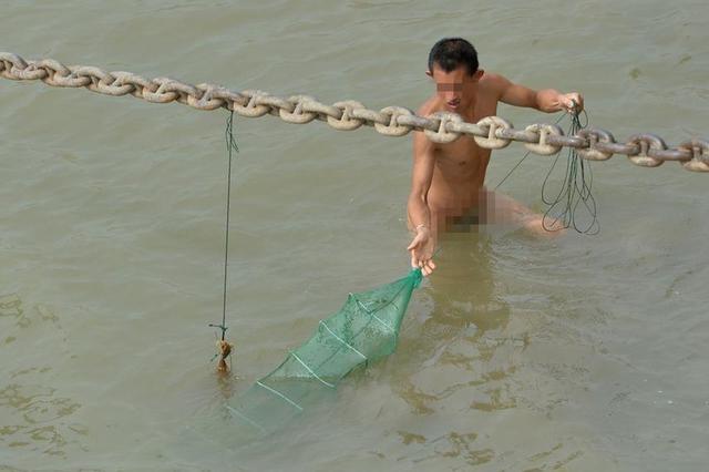 武汉一观光码头现裸男捕虾 无视周边游客
