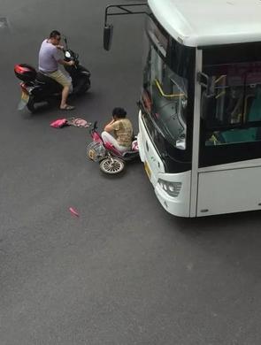 女子骑电瓶车过马路 被公交卷入车下