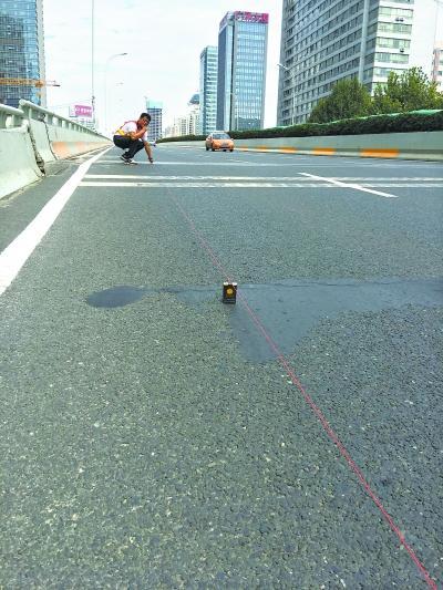 """徐东高架桥""""跳车""""处,技术人员测量面积和跳台落差高度。"""