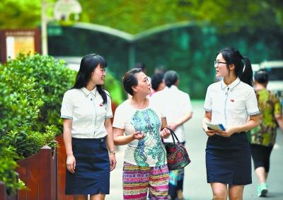黄埔人家小区,杨炯毅(左)、靳爽爽(右)同散步回来的居民周梦书(中)拉家常