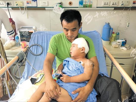 姚胜林正在照顾病床上的俊俊。
