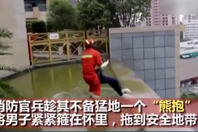 湖北宜昌一男子欲跳楼 消防队员熊抱救人