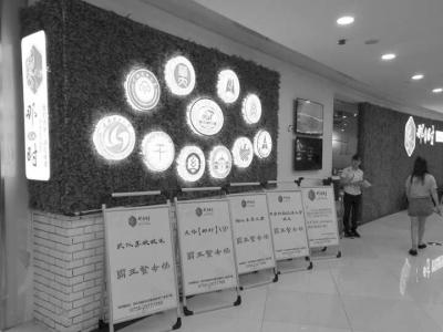 """""""那时·武汉""""的餐厅背景墙上有11所在汉高校的图标 刘晓芬供图"""