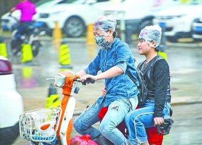 昨天,光谷珞新路附近,冒雨出行的市民  记者周迪 摄