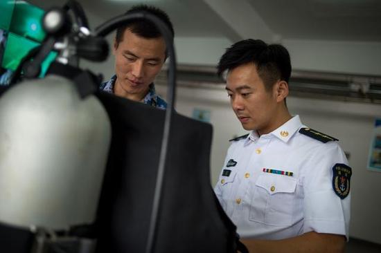 海军工程大学校内,官东和战友整理潜水装备 记者 任勇 摄
