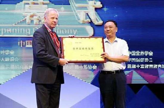 """国际茶叶委员会主席伊恩·吉布斯在开幕式上为恩施州授予""""世界富硒养生茶""""牌匾"""