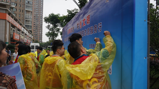 志愿者在承诺墙上签字
