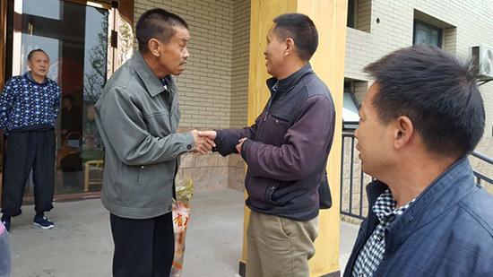 姜国良(左二)抓着弟弟的手不放。受访者供图