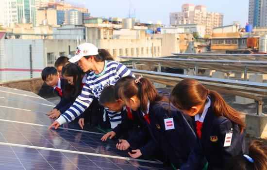 老师给学生讲解太阳能发电相关环保知识