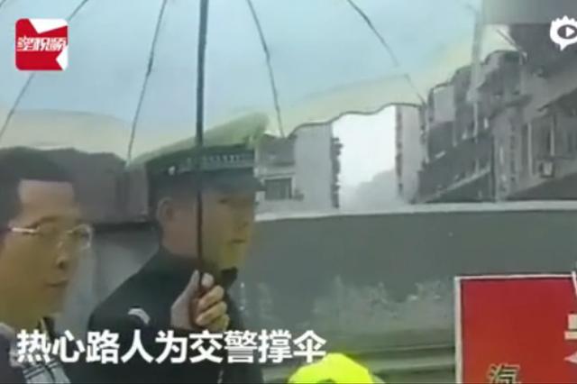 辅警脱衣护老人 两名路人给辅警撑伞