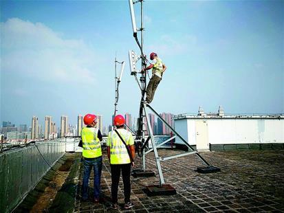 图为:上月,武汉移动公司工作人员在华中科技大学学生宿舍楼顶架设5G试验基站。