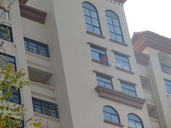 女子坐在17楼窗台上