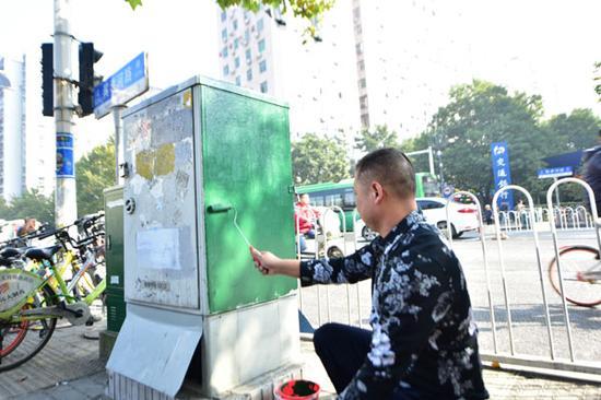 城管执法人员正在检查涂料的防治牛皮癣效果