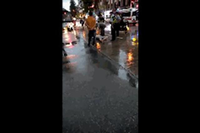 武汉一男子喝高了大雨中躺路上 警察将其带走醒酒