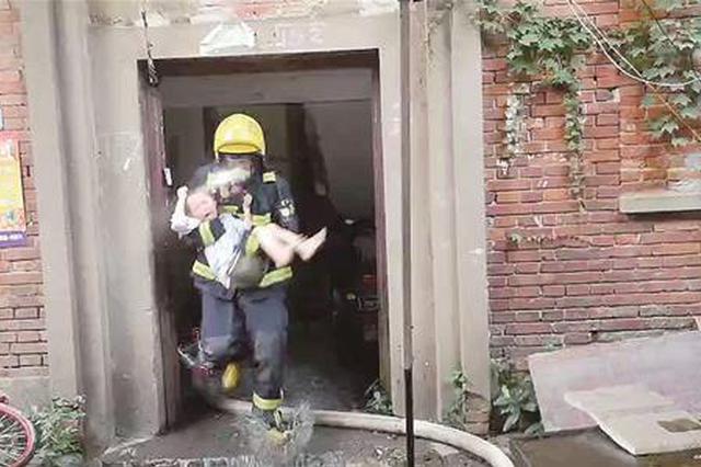 图为:一名消防官兵抱着被困的孩子冲下楼