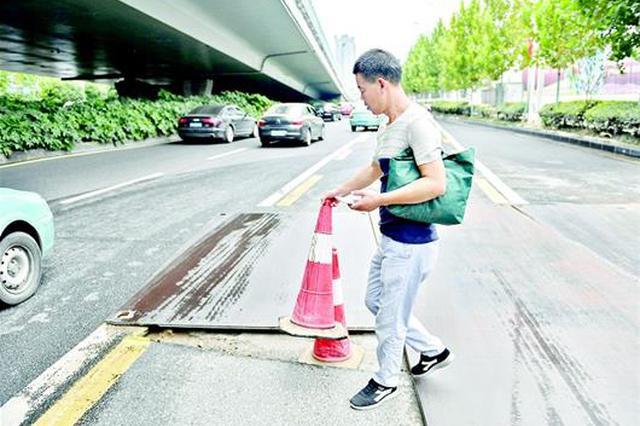 武汉一路面钢板翘起 露出路坑车辆路过戳破轮胎