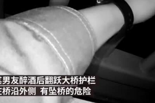 武汉一男子与女友吵架赌气坐长江大桥外侧 被民警拽回