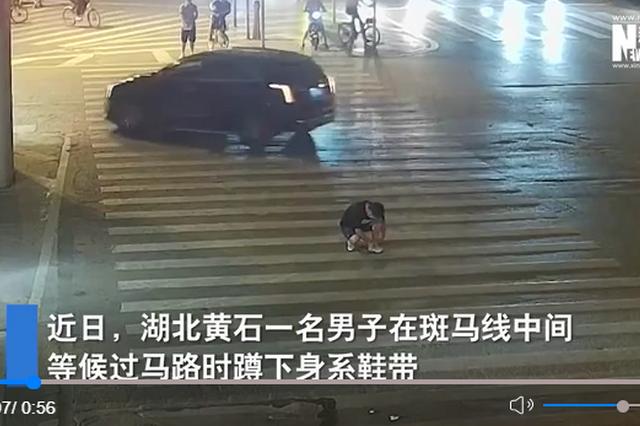 黄石一男子蹲斑马线系鞋带被卷入车底 警民合力抬车救人